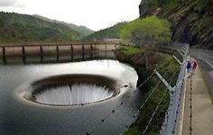 """Is this the result of dividing by zero?  Nope - this is the Morning Glory Spillway, also known as """"The Glory Hole"""".This Spillway, the largest in the world, is the funnel-shaped outlet that allows water to bypass the Monticello Dam in California when it reaches capacity (1370m³/s). The Glory Hole is located about 61m from the dam; the distance from the funnel to the exit point - which is situated in the south side of the canyon - is about 213m. The outside diameter is 22m, slowl"""