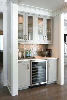 Kitchen Bar Area Contemporary living room bar nook is filled with gray glass front upper cabinets and gray shaker lower cabinets fitted with a glass front wine cooler paired with a white marble countertop and a gray glass linear tile backsplash. New Kitchen, Kitchen Decor, Kitchen Pantry, Kitchen Cabinets, Kitchen Ideas, Kitchen Backsplash, Awesome Kitchen, Wall Pantry, Kitchen Bars
