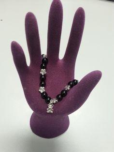 Pulsera negra con pequeños remaches entre medias plateados en forma de flor y un osito. Perfecta para cualquier ocasión.