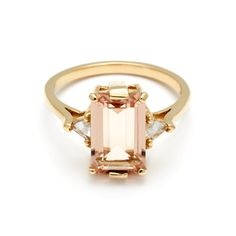 The Bea three stone ring features a stunning peach morganite centre which is set in an A.S. ceremonial signature basket- 10 prongs of mixed flat and delicate round. Inverted set trillion diamonds on each side lead the eye from the perfectly proportioned center to the subtly knife edge band.11x7mm (2.76ct) emerald cut peach morganite center with 0.26ctw white diamond trillions set in 14k yellowgoldThis ring is made to order within 4-6weeks.Requested modifications are subject to revised…