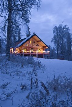 Log Cabin in the woods decorated with Christmas lights at twilight near Fairbanks, Alaska.