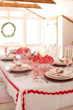 Red-and-white all over    Centerpieces of red-and-white carnations set the tone for this table. Complete the setting with clear glass jars filled with mints, peppermints scattered on the table, red-and-white ornaments and more.