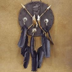 The symbol of protection, this Native American decorative shield dream catcher is adorned with feathers, buttons, and stone tipped arrows. An impressive decorative wall art piece for your dream catcher, shield, or arrow collection.