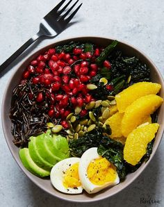 Buddha bowl with kale, avocado, orange and wild rice. Get the recipe for this healthy lunch.