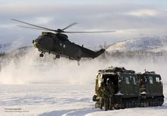 "Royal Navy Sea King Mk4 helicopter pilots and aircrews from Commando Helicopter Force (CHF) carry out a load lifting exercise as part of their Arctic flying training with a BV206 tracked vehicle standing by.  The training takes place some 200 miles inside the Arctic Circle at the Joint Helicopter Command (JHC) base near Bardufoss, Norway. The JHC base known as ""Clockwork"" provides survival and operational training and support facilities to enable aviation capable unit's arms to survive…"