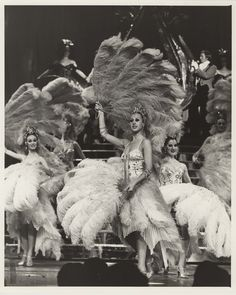 """Showgirls performing onstage with feather fans at the Sands Hotel and Casino in Las Vegas, circa 1970s-1980s.  Image is part of the UNLV Libraries """"Showgirls"""" digital collection."""