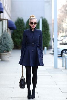 Bunned blonde hair, long-sleeve high-collar midthigh-length pleated-skirt navy dress, black leggings, black heels