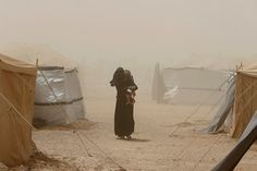 A woman, who fled from Falluja because of Islamic State violence, carries her child during a dust storm at a refugee camp in Ameriyat Falluja, Iraq