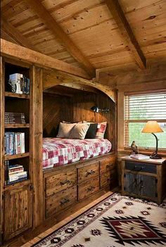 Space-saving built-in cubby-hole bed with six drawers underneath and adjacent shelves & cabinets, plus storage/display up top under the eaves.