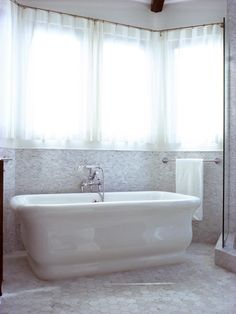 This classic white bathtub is accented with a neutral tile backsplash and sun-lit windows.