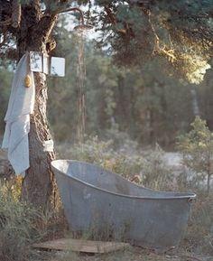 Zinken badkuip met douche onder de boom. Prachtige sfeer.