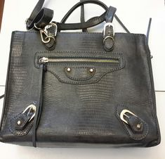 Beautiful Designer handbag in grey leather. One for shoulder and one for hand held. Accent designs with metal studs, buckles and tassels. Leather Interior, Balenciaga City Bag, Grey Leather, Designer Handbags, Studs, Shoulder Bag, Gray, Metal, Couture Bags