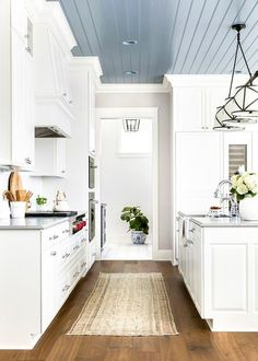 A Grosvenor Linear Triple Pendant hangs from a blue plank ceiling over a white k. A Grosvenor Linear Triple Pendant hangs from a blue plank ceiling over a white kitchen island boasting a farmhouse sink . Shiplap Ceiling, Plank Ceiling, Grey Ceiling, Colored Ceiling, Ceiling Decor, Ceiling Ideas, Blue Ceiling Bedroom, Accent Ceiling, White Ceiling Paint