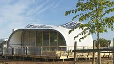 Techstyle Haus: An 800 sq ft Fabric Passive House That Uses 90% Less Energy Than Conventional Buildings. | The planters filter rainwater, then reused to grow edible plants. Photovoltaic panels are arrayed along the curved roof. Image © Kristen Pelou | Tiny Homes