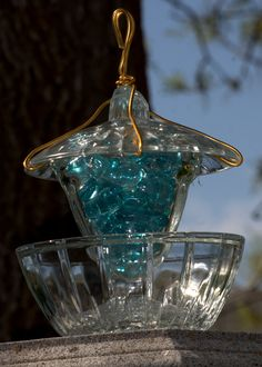 This is my version of the Bird Feeder! I used a candy dish, and a sunday dish filled will colored pebbles. Glued it all together with Loctite Stick'n Seal and wrapped wire around the top for the hanger!