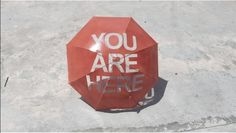 """You Are Here Umbrella  Nadiah Alsagoff is a multidisciplinary artist based in Singapore. For this project, she created a red umbrella with a concept directly inspired from the little location markers followed by the quote """"You are Here"""" directly incorporated to the wax cloth."""