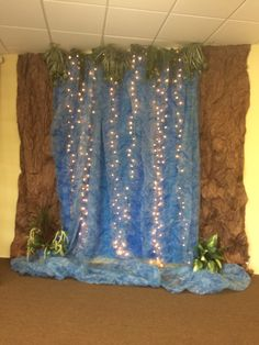 "My own waterfall. I'm so thrilled because I had all the materials on hand to make this one. 3 blue plastic tablecloths, wrinkled brown paper, ""water"" gossamer fabric, and two tired looking floral greenery pieces that I deconstructed for my ""plants""."