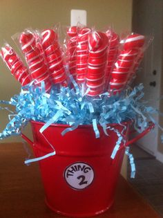 Cat in the hat birthday party- DIY candy buffet thing 1 thing 2 center piece  Dollar tree Bucket and foam floral, dollar tree lollipops  Dr. Seuss birthday party