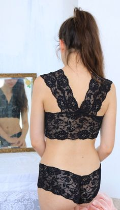 This gorgeous black lace bralette is designed with a sweet racer back and thick longline band under the bust for a supportive fit. The french knickers in the same lovely semi sheer floral lace have a flattering hipster fit. Bralette Sizing: Small A-C cup Medium C-E cup  Knicker sizing: Small 6-8 Medium 10-12 Large 14-16  Want to give this is a present? We gift wrap every purchase with tissue paper and vintage ribbon so that it arrives looking special.  Follow us: www.brightonlace.com…