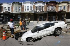 SINKING FEELING: People stood near a car whose front end fell Tuesday into a sinkhole that opened up overnight in the Hunting Park section of Philadelphia. No injuries were reported. (Matt Rourke/Associated Press)