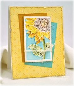 handmade card: Watercolored Sunflower from Thinking Inking ... luv the look of white embossed line art with watercolor details ... great colors (yellows, aquas and orange/brown) evoke a warm summer's day ... lie the casual way one layer is askew and the main background panel is distressed ... beautiful card!
