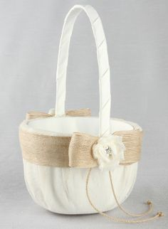 Miranda Flower Girl Basket: Perfect for your vintage or rustic themed wedding, this flower girl basket is covered with point d'esprit netting over satin. Jute trim is wrapped around and finished with a bow. A shabby flower is added to the jute trim and decorated with a pearl rhinestone flower for an elegant look.
