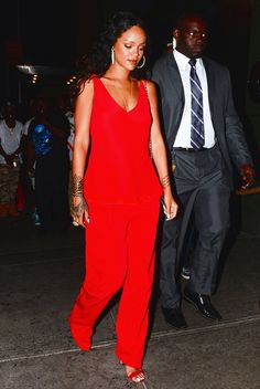 Rihanna rocks a red jumpsuit with matching Manolo Blahnik Chaos Ankle Strap Sandals during NYFW.