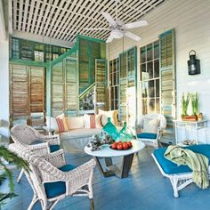 a porch with many salvaged shutters, a ceiling fan and cool blue painted floor