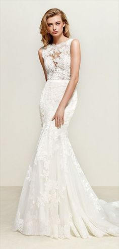 Pronovias 2018 romantic mermaid wedding dress with illusion neckline - Lace, tulle and satin take center stage in this romantic mermaid dress with illusion neckline. A bodice that blends into the skin creating a tattoo effect. The back in a deep V, edged in lace, is fitted to the waist with a discreet belt, leading to a magnificent skirt ending in a train.