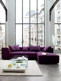 Wonderful Livingrrom Design Idea with Huge Size Glass Windows and Square Shaped White Carpet Floor and L Shaped Purple Sofa Set feat Small Purple Cushions and Glass Coffee Table with Lamp