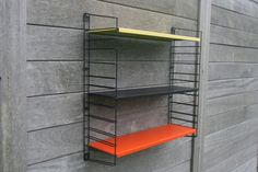 Vintage hanging Tomado book rack 1950-60. All parts are genuine vintage and signed Tomado Holland. In the original colors: red, black and yellow,