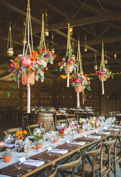 I LOVE this idea (and this barn looks exactly like our venue!) - Hanging potted flower arrangements at reception