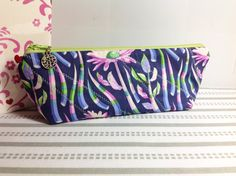 Inside Your Purse Pouch, Pencil Case, Cosmetic/Makeup Case, Phone Case, Navy Background, Pink Flowers on Stalks, Electric Polka Dots Lining, Stylish Stitching. Made with Tula Pink fabrics.  The shape of the case is sleek with curved corners at the top towards the zipper for a secure side-to-side closing. The bottom of the case has a flat bottom that allows it to stand on its on.