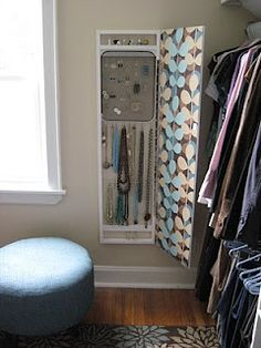 Jewelry storage behind full-length mirror. Rings are stored on pieces of wood dowel set into the pine framework, earrings hang from a metal bbq grill found on clearance and spray-painted brown, and S-hooks are used to hang necklaces from lengths of thin metal rod.