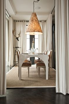 Hearst's designer visions showhouse has dark herringbone flooring, neutral jute area rug, a white dining table, leather chairs, floor to ceiling striped curtains, oversized patterned light fixture and ornate candle-sticks.