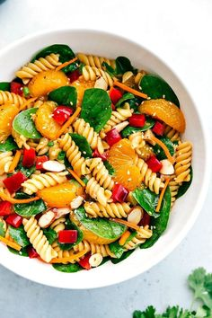 BEST ASIAN PASTA SALAD!! Pasta is tossed with spinach, mandarin oranges, lots ofveggies, sliced almonds, chicken and drizzled with a flavorful dressing. chelseasmessyapron.com