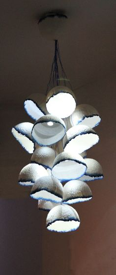 Finish-German designer Pia Wustenberg's Gunghat Light clusters.Textured paper half-domes tinted with a blue ink rim, clustered pendant. LED lights.