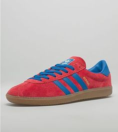 adidas Rouge OG: adidas Originals present this Rouge OG, a revival of one of their most iconic 'City Series' silhouettes. Presented in a red brushed suede upper, with blue accents to the three stripe branding, inner lining and heel panel. Featuring gold branding to the outer wall and printed brand graphic to the heel panel and tongue. The shoe sits upon a gum midsole and comes with both red and blue laces.