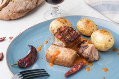 Aguja a la brasa y asadas: marinamos el cerdo en chiles africanos, vino blanco y limón. Lo asamos lentamente en el horno hasta que se tuesta quedando jugoso por dentro. Acompañamos de patatitas también asadas.
