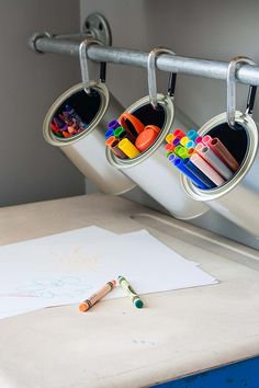 We love this wall-mounted craft caddy by Kelly Rinzema of The Lily Pad Cottage. It's an easy DIY project using galvanized pipe, paint cans and carabiners. It's great for keeping art supplies in a kid's room or a craft room!  || @krinze