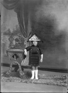 Studio portrait of an unidentified boy in fancy dress as a GR Post Office Letterbox, showing the boy standing next to a wooden high chair and resting his right arm on it, possibly Christchurch district