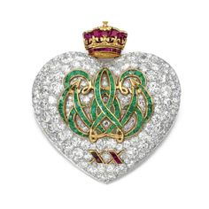 The pin was made to commemorate the couple's 20th Wedding Anniversary in 1957, designed by Cartier, Paris. Of heart-shaped design, applied to the centre with a monogram of the initials W and E set with calibré-cut emeralds, above the Roman numeral XX set with calibré-cut rubies, surmounted by a Royal Duke's coronet similarly set, to a background pavé-set with brilliant- and single-cut diamonds