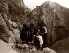 An educational picture of the Acoma Indians Among the Rocks. It was taken in 1905 by Edward S. Curtis.    The picture presents a Group of Acoma Indians, with pottery vessels at their feet, surrounded by rock formations.