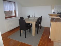 Next to the kitchen is a dining area with a wooden table seating for six. There's also a doorway to the balcony.
