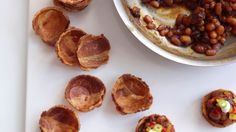 """Baked Beans in Bacon Cups <3 Instead of crumbling bacon bits into baked beans, this brilliant recipe takes a good idea and turns it upside down with amazing results. Baked beans served in individual bacon """"cups"""" are perfect party platter sides."""