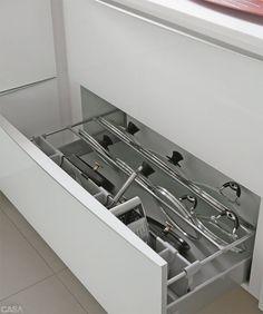 ESPAÇOSA E MUITO PRÁTICA. Sob toda a bancada em L, 17 gavetões guardam utensílios como talheres, travessas, panelas e até tampas, apoiadas em suportes que as mantêm organizadas.