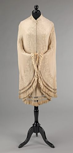 This is an excellent example of reconfiguring textiles to fit fashion. This dolman was created from a Chinese shawl, which was likely exported to the Philippines and then made into a fashionable garment in the United States when cumbersome shawls were no longer fashionable. The texture of the embroidery enlivens the muted tones of the textile and helps create an overall pleasing appearance.