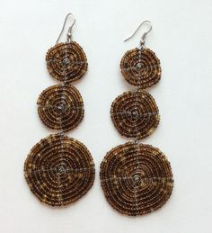 These earrings are handmade by Masai craftswomen in Kajiado County, Kenya. Although the earrings are crafted using traditional techniques, the designs are distinctly modern, so they complement your casual and formal looks beautifully. These two disc earrings measure 3.5 by 1.5 inches, and are the...