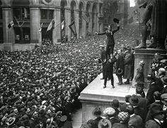 Charlie Chaplin being held by Douglas Fairbanks above crowd in Wall Street, NY, 1918