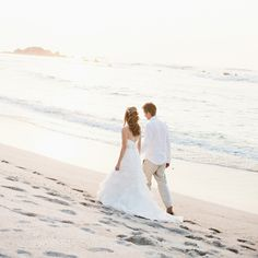 The couple stroll along the ocean as husband and wife.